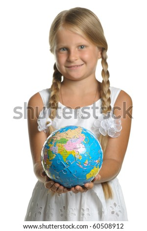 The girl holds the globe collected from puzzle in hands. Selective focus. It is isolated on a white background
