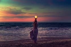 The girl holds the moon in her hands. Beautiful sunset on the sea. Dreams come true. Everything is possible.