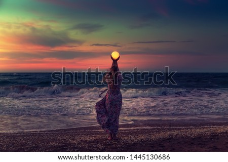 The girl holds the moon in her hands. Beautiful sunset on the sea. Dreams come true. Everything is possible. Сток-фото ©
