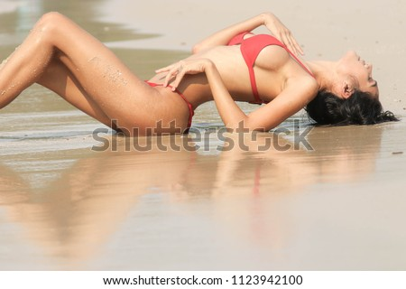 The girl in a bikini on the beach, there is a red shadow reflected on the water. #1123942100