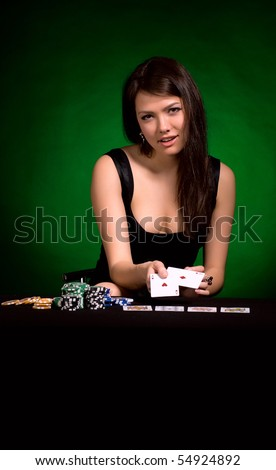 The girl in a black dress with cards on a green background