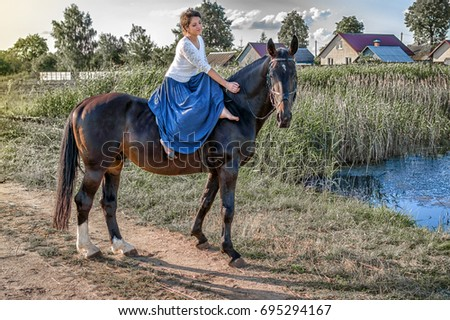 Stock Photo the girl in a blue skirt astride a horse