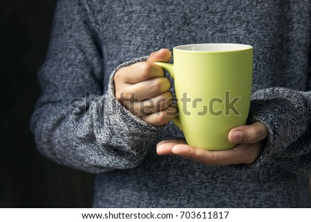 The girl in a cozy knitted sweater holding hot cup of coffee or tea in cafe or living room. #703611817