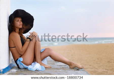The girl in a hat sits