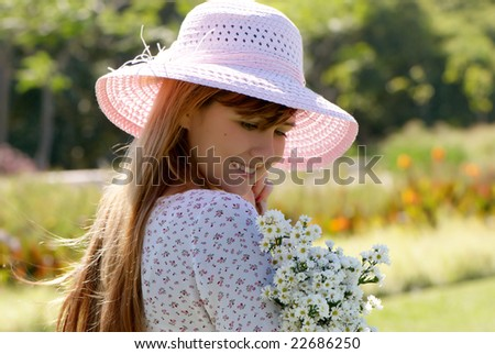 The girl in a hat with a bunch of flowers