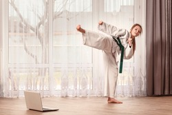 The girl in a kimono stands in a fighting position. The child trains karate at home in front of a laptop. A taekwondo fighter kicks.