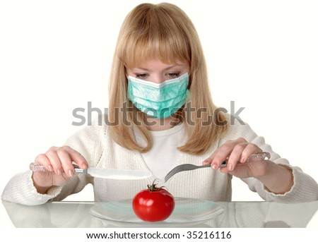 The girl in a medical mask tries to cut a tomato