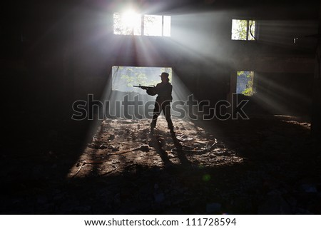 The girl in a military uniform with a rifle in the ruins