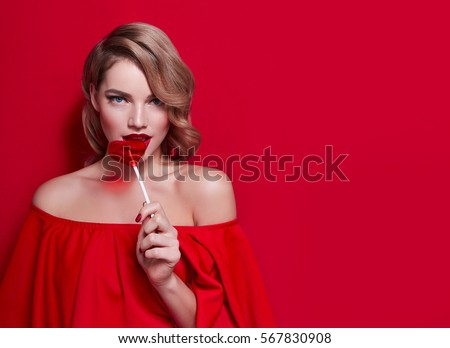 The girl in a red dress on a red background in the studio. Blonde girl holding a red heart-shaped lollipop. Valentine's Day. Advertising. Girl holding a lollipop in his mouth.