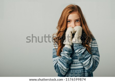 The girl in a sweater with red horns smiles, warming her face with gloves on her hands. Warm knitted gloves turned out to be very warm and warmly warm her hands. Isolated white background