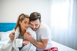 The girl in bathrobe sitting on the bed feeling sick while man taking care of her. Young woman in bed with cold and flu, she is blowing her nose, her boyfriend is giving her an hot drink