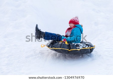 The girl in blue clothes with red hat and scarf descending from the hill covered with a snow on the black rubber ring instead of sledge. The winter picture of holiday recreation
