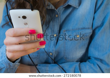 The girl in blue denim shirt with red nail Polish listens to music on a white phone.