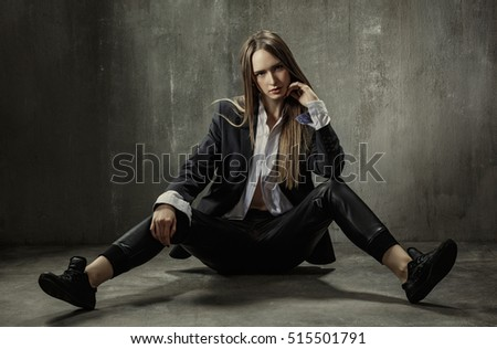 The girl in classic jacket, blouse and leather pants sits on a background of gray concrete wall #515501791