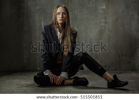 The girl in classic jacket, blouse and leather pants sits on a background of gray concrete wall #515501851