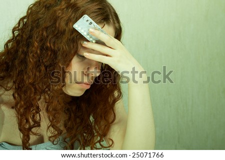 The girl in confusion holds contraceptive tablets in hands