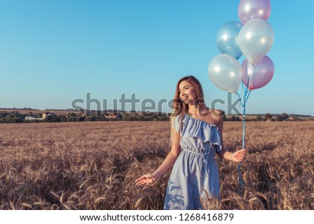 The girl in field bright sunny day. In hands holding balloons. Smiles happily and looks into distance. Free space for text. The concept of gift and holiday. Emotions pleasure of pleasure and joy.