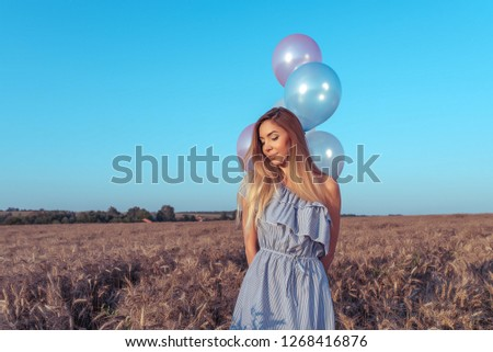 The girl in field bright sunny day. In hands of holding balloons. Happily smiles, dreams and dreams. Free space for text. The concept of gift holiday. Emotions are pleasure of pleasure and tenderness.