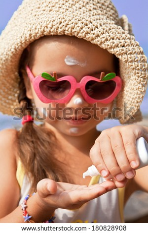 The girl in glasses gets on the palm of sunscreen