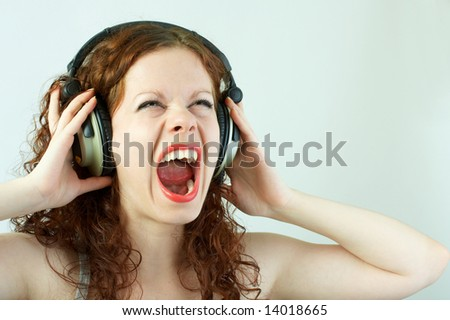 The girl in headphones shouts on a white background - stock photo