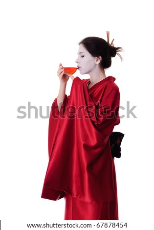 The girl in native costume of japanese geisha drinking black tea, isolated on white