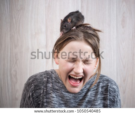 The girl in panic shouting. On her head sits a rat. The concept of a phobia, a fear of rodents, inner fears, hallucinations #1050540485