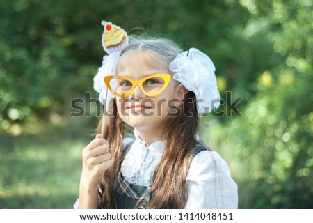b676e3600d5c The girl in school uniform holds glasses in front of her eyes. On the head