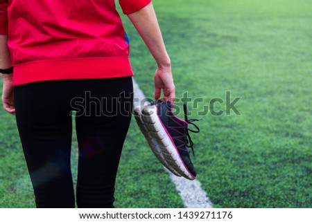 The girl in sportswear walks through the stadium and holds sneakers in her hands.