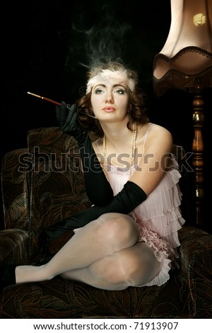 The girl in style 30 on an armchair - stock photo