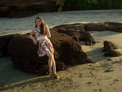 the girl in the dress around the rocks at the beach