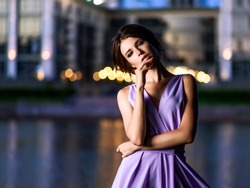 The girl in the dress on the lake. Nature. Purple dress develops on the fly. Long, beautiful legs, nice hair. Green grass. Deep sunset sky.