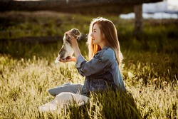 The girl in the field holds a rabbit in her arms, she hugs him and plays with him. Girl with long hair in a denim jacket. Image with selective focus