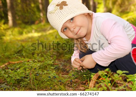 The girl in the forest, collecting berries