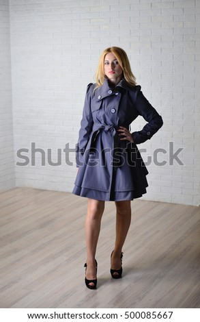 The girl in the grey coat in the Studio. The image of a fashionable girl. Outerwear #500085667