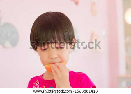 The girl in the pink shirt, black hair, eating orange has a sour taste close eyes because sour taste. Picture pink tone.