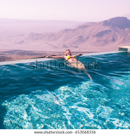 The girl in the pool amid a beautiful mountain landscape