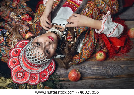 The girl in the red headdress and Russian folk style among apples on dark wooden background top view #748029856