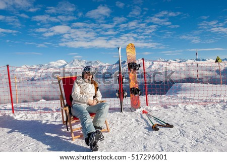 Shutterstock The girl in the ski lounger. The skier sits in a mask and helmet lay next to skis and a snowboard. Recreation area at the peak of the slope of Rosa Khutor. Blue sky and Sunny weather.