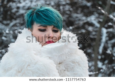 Stock Photo The girl in the snowy park wrapped herself in a white woolen plaid can only see the eyes and blue hair. She warms her nose and hands