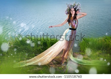 The girl in the wreath stands against the backdrop of beautiful scenery