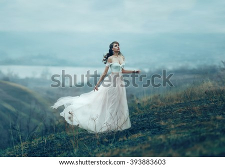 The girl in transparent dress with long flying pastel train stands on the top of the mountain , Shabby chic, boho style , fashion creative computer color rendering  #393883603
