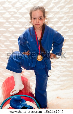 The girl is a fighter. A girl at the age of 6 in a blue kimano with a gold medal and injuries (make-up) is standing next to sports equipment