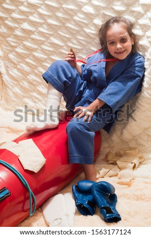The girl is a fighter. A girl at the age of 6 in a blue kimano with a gold medal and injuries (make-up) is next to sports equipment