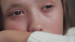 The girl is crying in the room sitting at the table and tears are flowing from her eyes. The transitional age of adolescents and the unbalanced psyche of the child. The experiences and failures of the