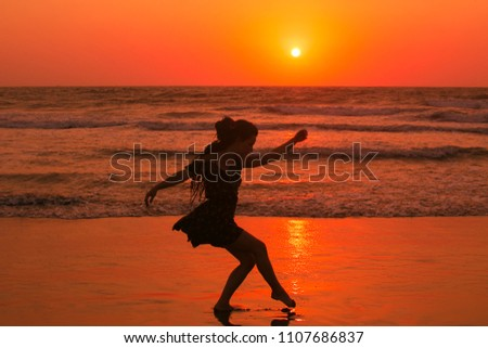 The girl is doing the movements at the seaside. Feeling light and elegant dancing, orange lights illuminates her silhouette. #1107686837