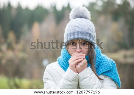 The girl is dressed in warm clothes, warm hands. Autumn, cold outside #1207797196