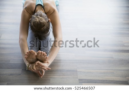 The girl is engaged in yoga indoors