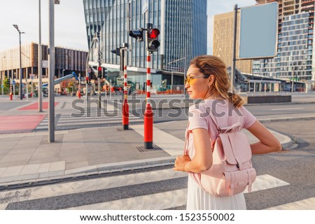 The girl is going to cross the road on a prohibiting red light. Road traffic safety concept