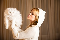 The girl is holding a fluffy white cat