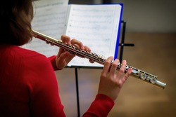 The girl is holding a large concert flute (in hands close-up). Professional musician at the rehearsal. A woman plays the transverse flute.